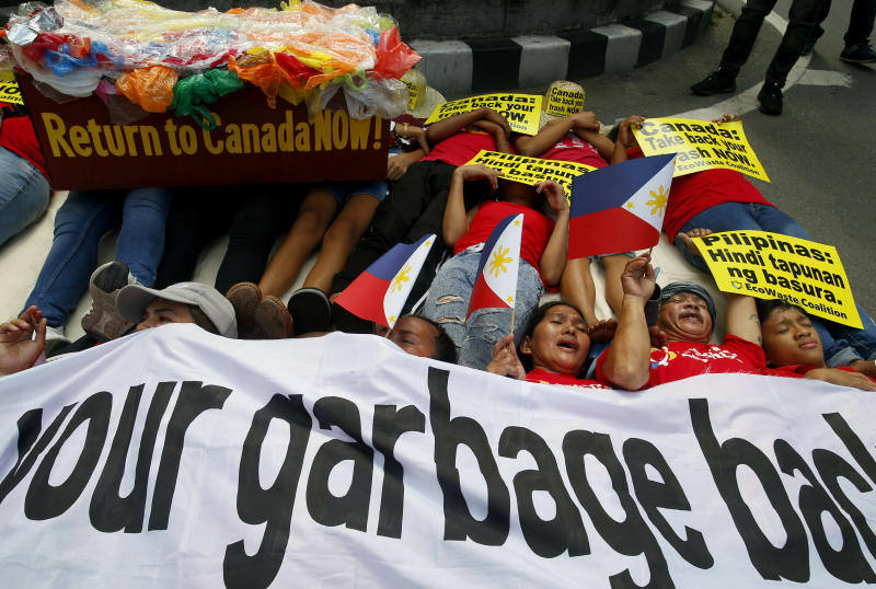 Environmentalists stage a mock die-in protest outside the Canadian Embassy to demand the Canadian government to speed up the removal of several containers of garbage that were shipped to the country Tuesday, May 21, 2019, in Manila, Philippines. The Philippines recalled its ambassador and consuls in Canada last week over Ottawa's failure to comply with a deadline to take back 69 containers of garbage that Filipino officials say were illegally shipped to the Philippines years ago. (AP Photo/Bullit Marquez)