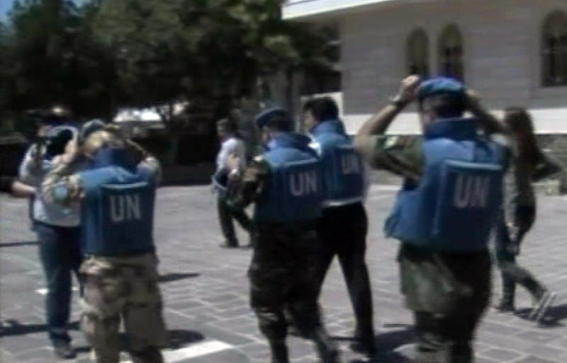 This image made from video made available by Syrian TV shows United Nations observers during a visit to Homs, Syria, Saturday, April 21, 2012. Five U.N. truce monitors ventured Saturday into the heart of the Syrian uprising, one of the hardest-hit opposition strongholds, and were thronged by residents clamoring for foreign military help to oust President Bashar Assad. Activists said Homs, which has been battered by tank and mortar shells fired by regime forces for weeks, was relatively calm during the visit, except for the sound of sporadic gunfire, and that troops pulled armored vehicles off the streets.(AP Photo/Syria TV via AP video) TV OUT SYRIA OUT