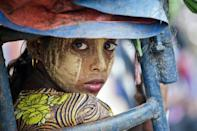 In this file photo taken on May 21, 2015, an ethnic Rohingya Muslim woman looks back as she rides a 'tuk tuk' near a camp set up outside the city of Sittwe in Rakhine state