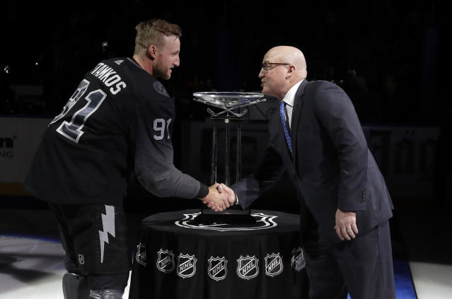NHL Deputy Commissioner Bill Daly, right, shakes hands with Tampa Bay Lightning's Steven Stamkos (91) after presenting the team with the President's Trophy before an NHL hockey game Saturday, March 30, 2019, in Tampa, Fla. (AP Photo/Chris O'Meara)