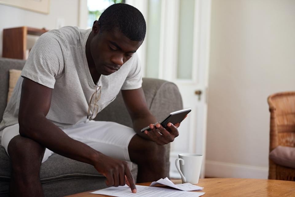 black or african-american man using a calculator to make a bill payment