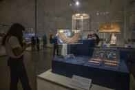 FILE - In this April 24, 2021 file photo, women look at a collection of the jewelry of Princess Neferuptah, the daughter of King Amenemhat III, on display in its glass case at the new National Museum of Egyptian Civilization in Old Cairo. As some European countries re-open to international tourists, Egypt has already been trying for months to attract them to its archaeological sites and museums. Officials are betting that the new ancient discoveries will set it apart on the mid- and post-pandemic tourism market (AP Photo/Nariman El-Mofty, File)