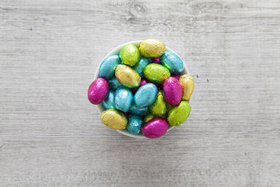 Brightly colored foil wrapped mini Easter eggs in a ramekin dish photographed from overhead