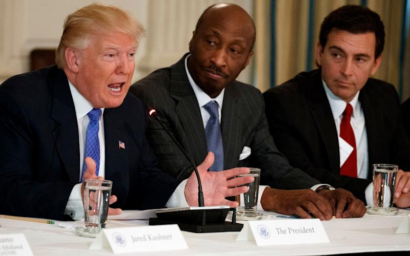 Ken Frazier, seated next to Donald Trump in January, was the first CEO to resign in response to his handling of Charlottesville - AP