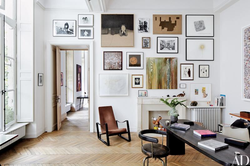The Paris apartment of design dealers Laurence and Patrick Seguin features a wall of artworks by Richard Kern, David Noonan, Sam Durant, Carol Bove, and others. Pierre Jeanneret and Charlotte Perriand designed the desk and swivel chair; the lounge chair is by Jean Prouvé.