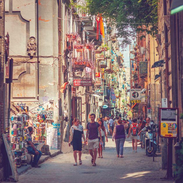 Naples, Italy - July 28, 2015: Narrow street in the center of Naples, with its traditional architecture, cafes and shops. Locals and tourists are walking through.
