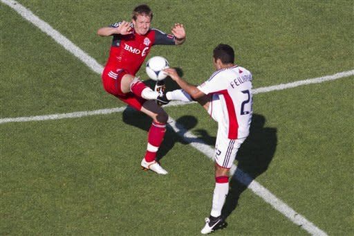 Toronto FC 's Terry Dunfield, left, battles for the ball with New England Revolution's Benny Feilhaber during first half MLS soccer action in Toronto on Saturday June 23, 2012. (AP Photo/The Canadian Press, Chris Young)