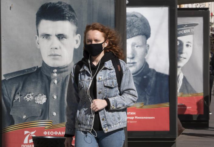 A woman wearing a face mask to protect against coronavirus walks past posters with portraits of the Soviet Army soldiers, participants in World War II during celebration of the 75th anniversary of the defeat of the Nazis in World War II in St.Petersburg, Russia, Saturday, May 9, 2020. Victory Day, the anniversary of the defeat of Nazi Germany in World War II, is Russia's most important secular holiday and this year's observance had been expected to be especially large because it is the 75th anniversary, but military parades in Russian cities and a mass processions called The Immortal Regiment were postponed as part of measures to stifle the spread of coronavirus. (AP Photo/Dmitri Lovetsky)