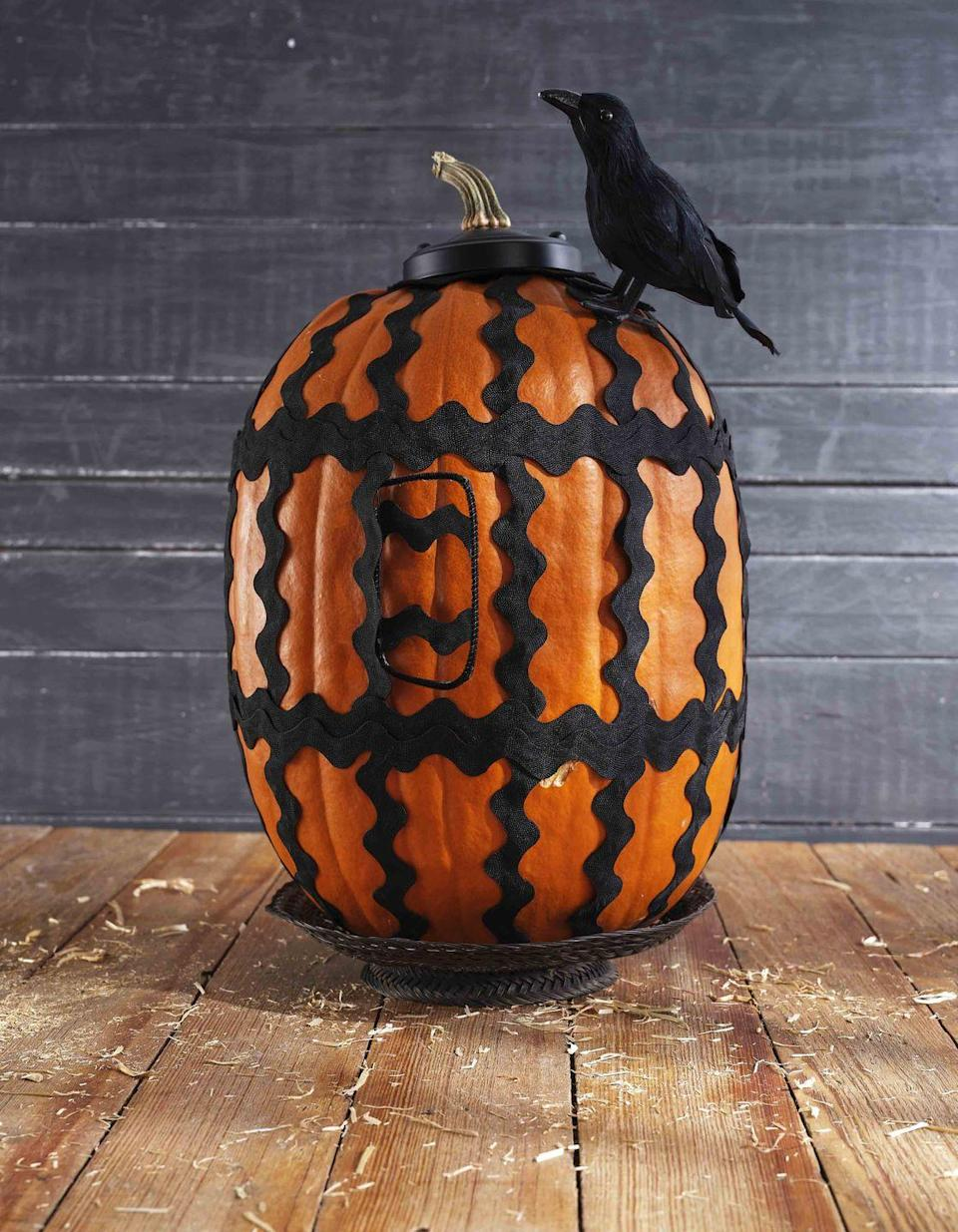 <p>Wrap and oblong pumpkin with large black rickrack to create the wires of a spooky birdcage. Friendly crow optional!<strong><br></strong></p><p><strong>Make the pumpkin:</strong> Remove the stem from a large oblong pumpkin; reserve. Attach lengths of large rickrack to the top and bottom of the pumpkin, spacing evenly, with hot-glue. Attach two double layers of large rickrack horizontally at the bottom and top third with hot-glue. Fashion a door from black pipe cleaner, and attach lengths of rickrack to the back; wedge under one of the vertical lengths of rickrack. Attach pumpkin stem to the center of a black ceiling light canopy, and place on top of pumpkin. Hot-glue a toy crow to the pumpkin and set on a black plate or cake stand. </p>