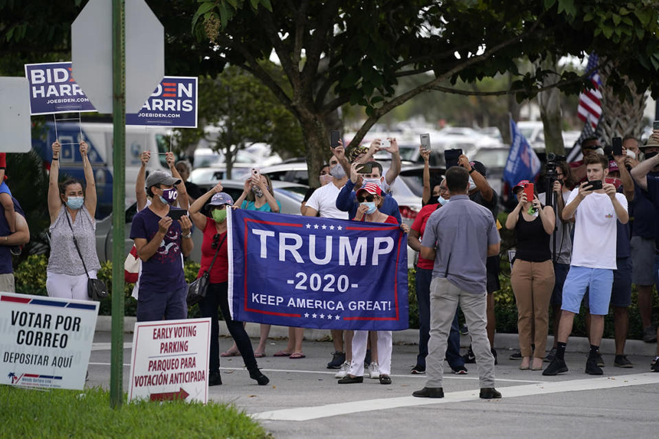 People wait outside a West Palm Beach, Fla., library on Saturday as President Donald Trump casts his ballot for the presidential election.