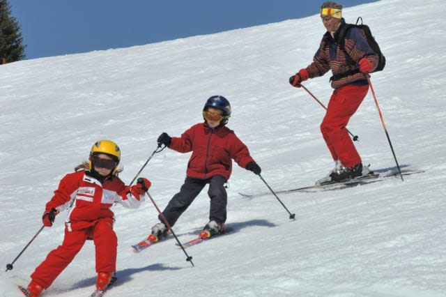 Father and children skiing