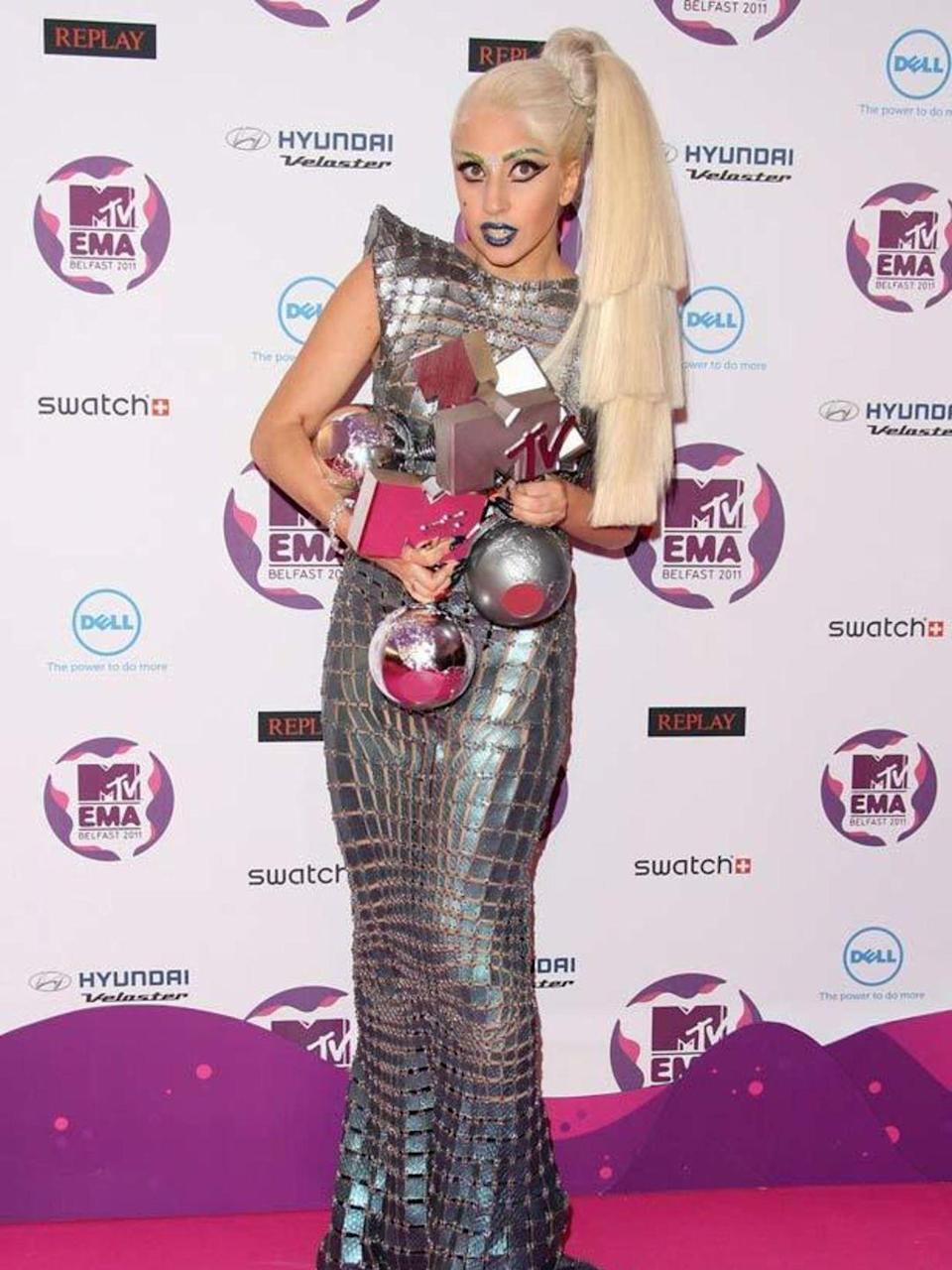 """<p>Lady Gaga works the space-age look with this metallic <a href=""""http://www.elleuk.com/catwalk/collections/paco-rabanne/"""" rel=""""nofollow noopener"""" target=""""_blank"""" data-ylk=""""slk:Paco Rabanne"""" class=""""link rapid-noclick-resp"""">Paco Rabanne</a> S/S 12 dress, slicked back ponytail and blue and silver makeup for the MTV Europe Music Awards in Ireland, November 2011.</p>"""