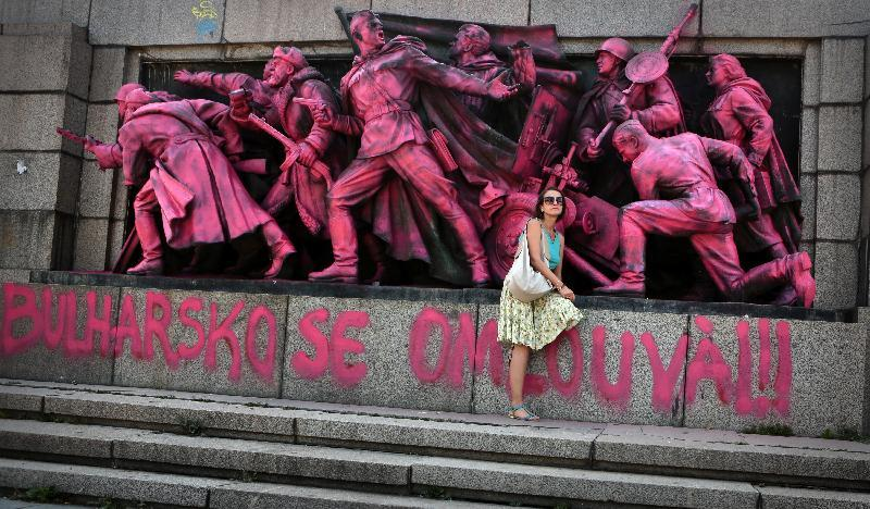 "A woman poses for a photograph next to a Soviet Army monument colored pink by unknown people to mark the anniversary of the Prague Spring with an inscription in Bulgarian and Czech below reading ""Bulgaria apologizes."" in Sofia, Wednesday, Aug. 21, 2013. Bulgaria, which marched in lock step with the Soviet Union for decades, was the first country to insist on the invasion and the last one to formally apologize for its participation – with a declaration of Parliament in 1990, and in 1997, during a presidential visit to Prague. (AP Photo/Valentina Petrova)"