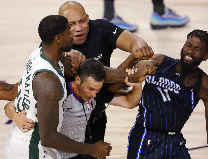 Milwaukee Bucks' Marvin Williams grabs the jersey of Orlando Magic's James Ennis III as referee Kevin Scott and Bucks assistant coach Darvin Ham tries to break it up during Game 3. (Mike Ehrmann/Pool Photo via AP)