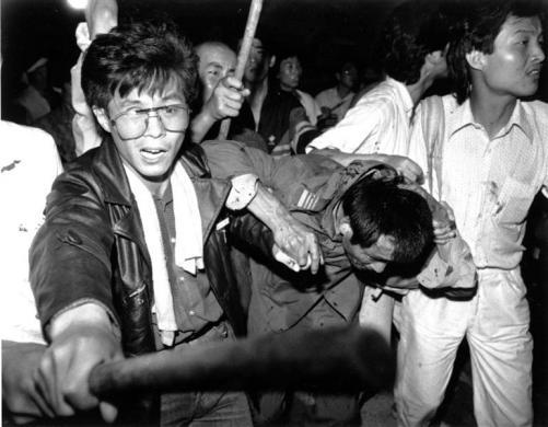 A captured tank driver is helped to safety by students as the crowd beats him, June 4, 1989.