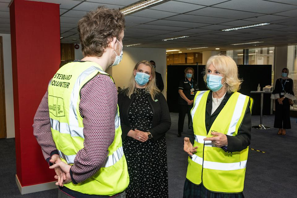 LONDON, ENGLAND - FEBRUARY 23: Camilla, Duchess of Cornwall, Royal Voluntary Service President, speaks to James Leggett, a NHS Volunteer Responder Steward at Wembley Vaccination Centre on February 23, 2021 in London, England. (Photo by Philip Hartley-WPA Pool/Getty Images)