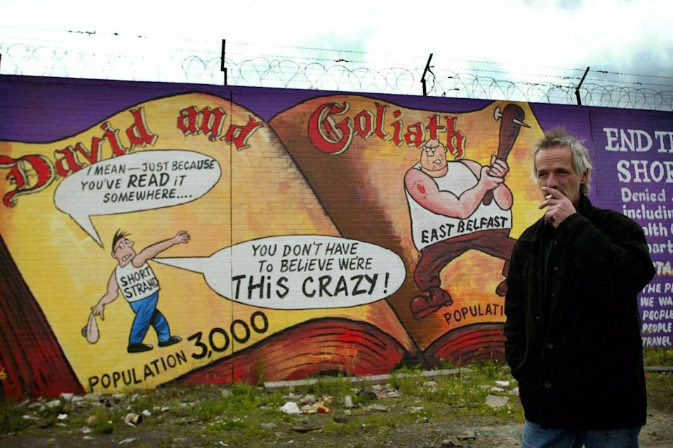 Danny Devenny stands in front of his work depicting nationalists as David and loyalists as Goliath in the Short Strand area of Belfast, July 2002Alamy