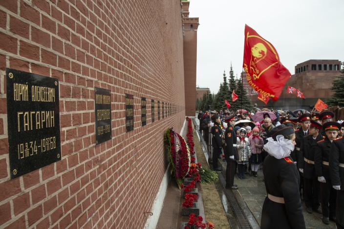 FILE - In this Friday, April 12, 2019 file photo, people queue to lay flowers at a grave of Yuri Gagarin, the first person who flew to space, in the Kremlin wall Cosmonauts Day, in Moscow, Russia. After Gagarin died in a training jet crash in March 1968, he was buried near the Kremlin Wall alongside Soviet leaders. From a giant statue towering over Moscow to a more modest monument on the Sakhalin Island in the Pacific Ocean, dozens of memorials across Russia commemorate Yuri Gagarin, the cosmonaut who became the first person in space on April 12, 1961, 60 years ago. (AP Photo/Alexander Zemlianichenko, File)