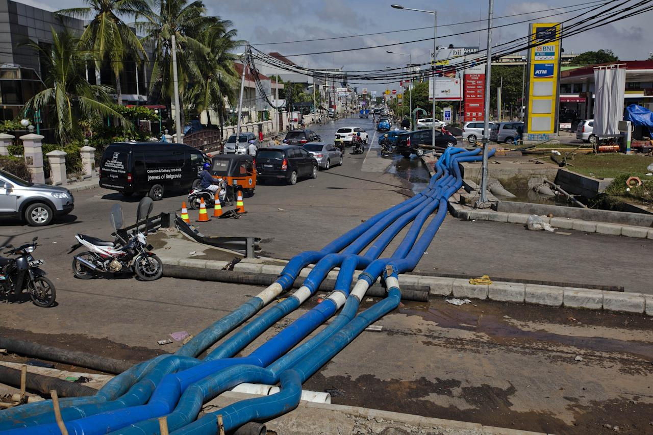 JAKARTA, INDONESIA - JANUARY 26:  Pipes from a  water pump lay across a street during the  clean-up of floodwaters in North Jakarta on January 26, 2013 in Jakarta, Indonesia. With heavy rain forecast for January 26-28, Indonesian authorities have organised the use of generators and cloud-seeding measures to defuse rain-laden clouds to help prevent further flooding of Jakarta, following last week's floods which claimed the lives of 32 people.  (Photo by Ulet Ifansasti/Getty Images)