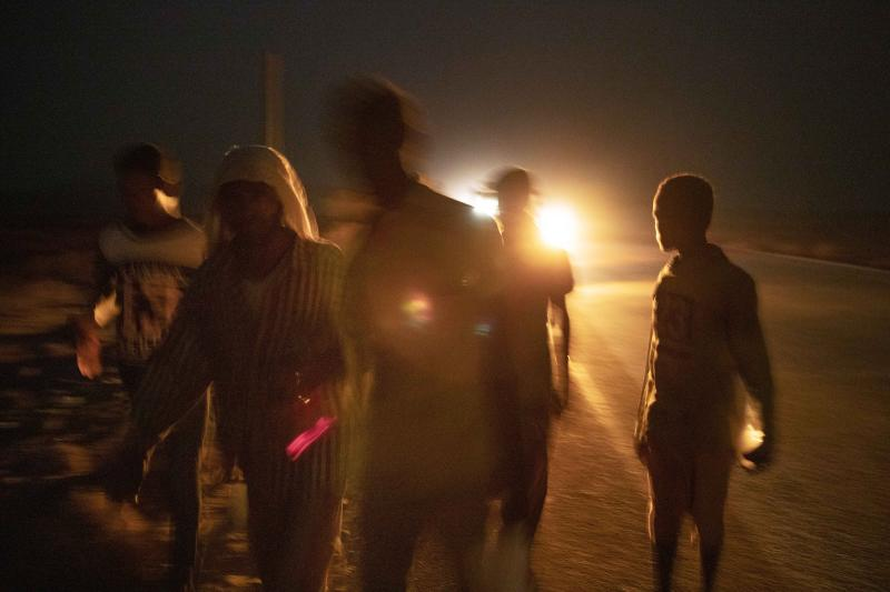 "In this July 12, 2019 photo, 35-year-old Mohammed Eissa, second left, walks on a highway with boys he met on the way, around 50 kilometers (31 miles) from Djibouti. Eissa had left behind his wife, nine sons and a daughter. His wife cares for his elderly father. The children work the farm growing vegetables, but harvests are unpredictable: ""If there's no rain, there's nothing."" (AP Photo/Nariman El-Mofty)"