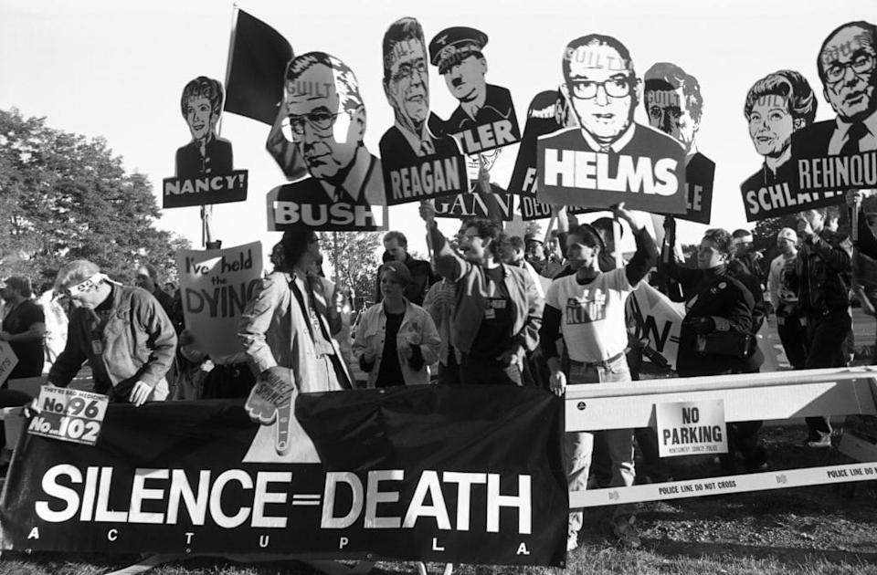 Members of AIDS activist group ACT UP (AIDS Coalition to Unleash Power) hold up signs of George W. Bush, Ronald Reagan, Nancy Reagan, Jesse Helms and other with the word 'Guilty' stamped on their foreheads. (Catherine McGann/Getty Images)