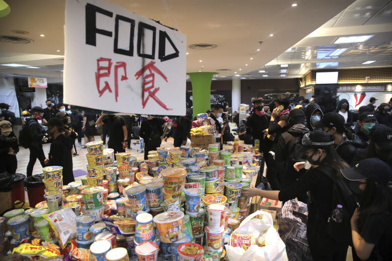 Protestors take instant noodles from a pile of food at Hong Kong Polytechnic University in Hong Kong, Thursday, Nov. 14, 2019. Hong Kong residents endured traffic snarls and mass transit disruptions Thursday as protesters closed some main roads and rail networks while police skirmished with militant students at major universities. (AP Photo/Kin Cheung)