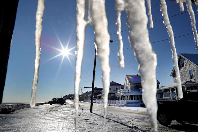 <p>Icicles hang from a porch on Ocean Street as cleanup takes place in the Brant Rock section of Marshfield, Mass., following a winter storm that flooded much of the area the previous day, on Jan. 5, 2018. (Photo: John Tlumacki/The Boston Globe via Getty Images) </p>