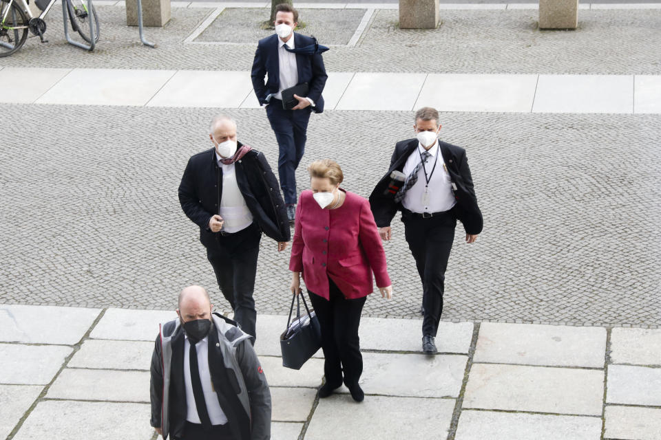 German Chancellor Angela Merkel, center, arrives for a parliament session about a new law to battle the coronavirus pandemic at the Bundestag at the Reichstags building in Berlin, Germany, Friday, April 16, 2021. (AP Photo/Markus Schreiber)