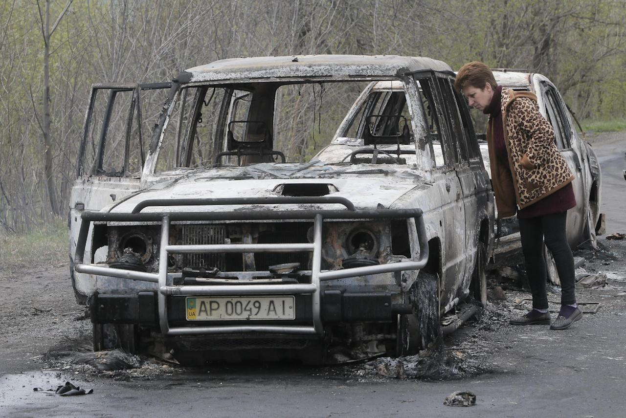 A local resident inspects burnt-out cars after night fight at the checkpoint which under control of pro-Russian activists in the village of Bulbasika near Slovyansk on Sunday, April 20, 2014. Pro-Russian insurgents defiantly refused to surrender their weapons or give up government buildings in eastern Ukraine, despite a diplomatic accord reached in Geneva and overtures from the government in Kiev. (AP Photo/Efrem Lukatsky)