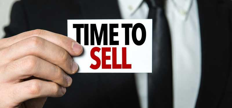 man in business suit holding sign that says time to sell