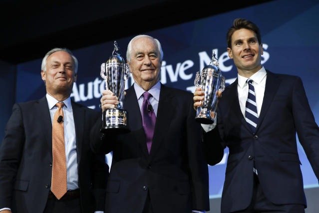 "Fred Lissalde, left, president and CEO of BorgWarner; Roger Penske, team owner; and Will Power, right, winner of the 2018 Indianapolis 500, hold their ""Baby Borg"" driver's and team owner's trophies in Detroit, Wednesday, Jan. 16, 2019. (AP Photo/Paul Sancya)"