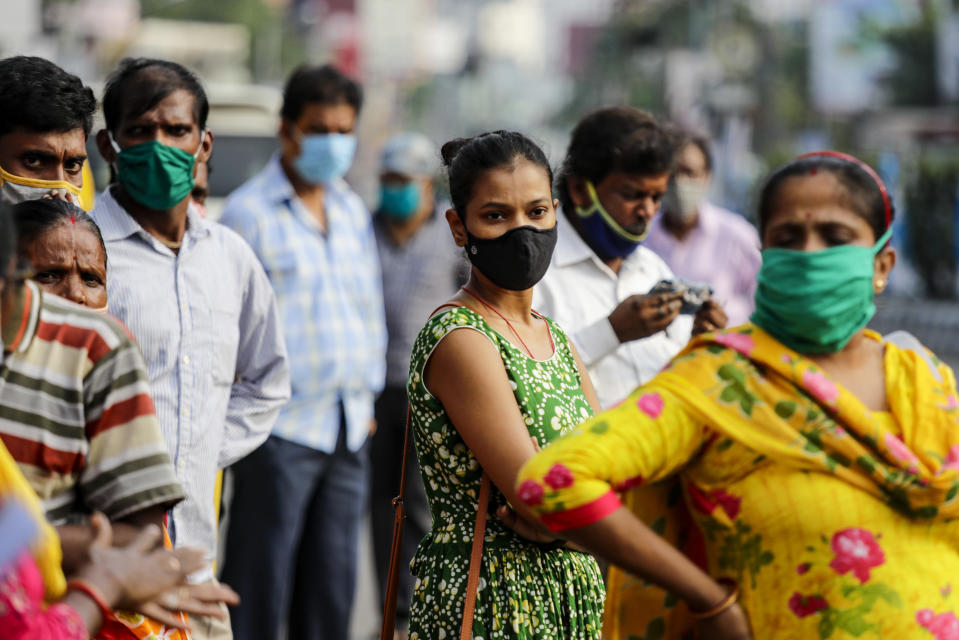 Commuters with face mask to prevent the spread of the coronavirus wait for a bus in Kolkata, India, Saturday, Oct. 10, 2020. India's total coronavirus positive cases near 7 million with another 73,272 infections reported in the past 24 hours. The Health Ministry on Saturday put the total positive caseload at 6.97 million, second to 7.66 million infections registered in the worst-hit United States. (AP Photo/Bikas Das)
