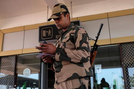 FILE PHOTO: A Border Security Force (BSF) soldier checks the passport of an Indian passenger from the 'friendship bus' between Indian and Pakistan at the Wagah-Attari border crossing, India, March 15, 2019. REUTERS/Alasdair Pal