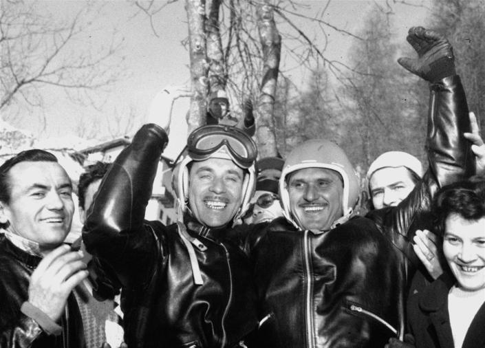 "FILE - In this Jan. 28, 1956 file photo, Italy's Giacomo Conti, right, brakeman, and driver Lamberto Dalla Costa, smile and wave after winning the two-man bobsled championship of the Winter Olympics at Cortina D'Ampezzo, Italy. The Cortina track was built in 1923 and the resort known as the ""Queen"" of the Italian Dolomites was home to bobsledding great Eugenio Monti, who won six Olympic medals between 1956 and 1968. (AP Photo, File)"