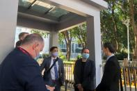Consulate representatives stand at an entrance to a court in Shenzhen