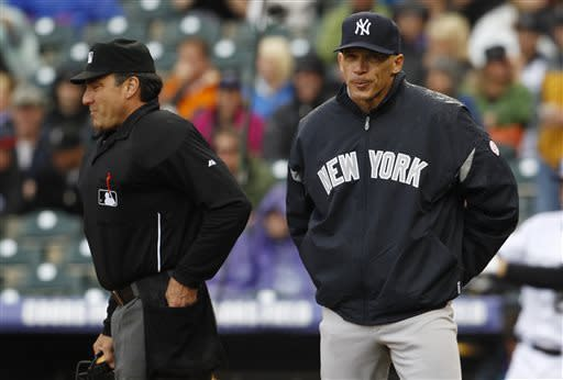 New York Yankees manager Joe Girardi, right, reacts after arguing with home plate umpire Phil Cuzzi, who called Colorado Rockies runner Dexter Fowler safe at home as he scored on a sacrifice fly in the first inning of a baseball game in Denver on Thursday, May 9, 2013. (AP Photo/David Zalubowski)