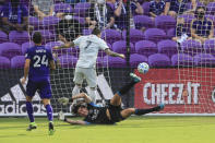 New England Revolution forward Gustavo Bou (7) scores a goal past Orlando City goalkeeper Brian Rowe, bottom, during the first half of an MLS playoff soccer match, Sunday, Nov. 29, 2020, in Orlando, Fla. (AP Photo/Matt Stamey)