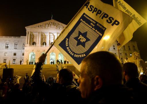 A demonstrator waves the flag of the Association of Professional Police Officers during a protest against the government's austerity measures outside Parliament in Lisbon on November 12, 2013