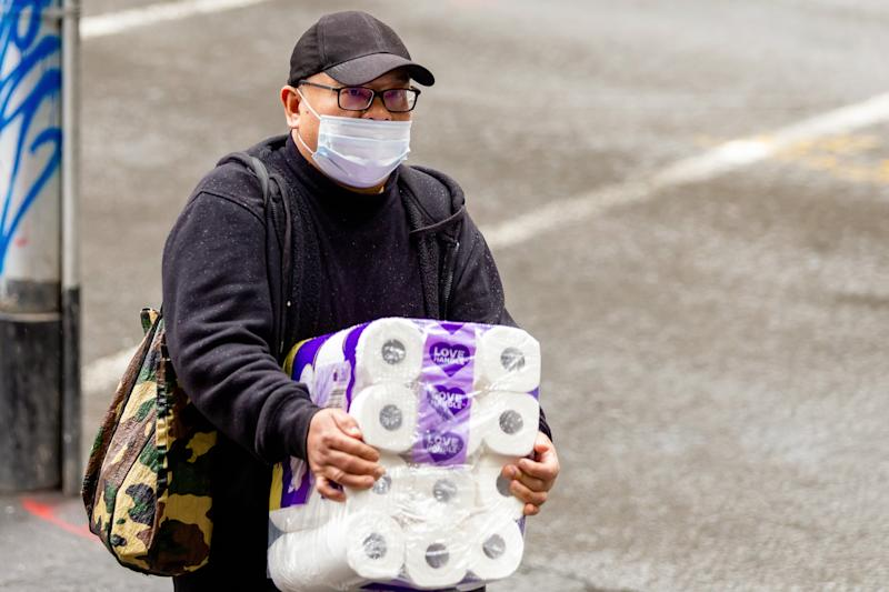 MELBOURNE, AUSTRALIA - MAY 09: A man wearing a face mask carries a large pack of toilet paper in the CBD during the Coronavirus (COVID-19) pandemic on May 09, 2020, in Melbourne, Australia. (Photo by Speed Media/Icon Sportswire)