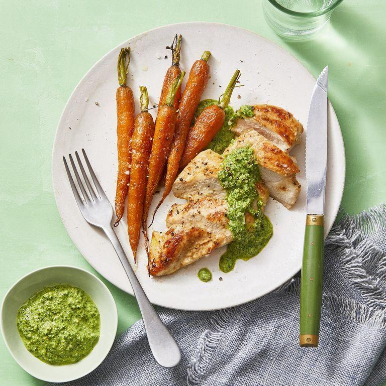 """<p>The simplicity of this dish doesn't take away from its powerful flavors. All you need is 25 minutes, a few ingredients you probably have laying around the house to make the vibrant sauce that is perfect on chicken, fish, or pork. <br></p><p><em><a href=""""https://www.womansday.com/food-recipes/a30393899/seared-chicken-with-carrots-and-mint-almond-pesto-recipe/"""" rel=""""nofollow noopener"""" target=""""_blank"""" data-ylk=""""slk:Get the Seared Chicken with Carrots and Mint-Almond Pesto recipe."""" class=""""link rapid-noclick-resp"""">Get the Seared Chicken with Carrots and Mint-Almond Pesto recipe.</a></em></p>"""