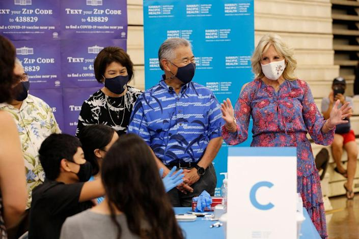 Hawaii Gov. David Ige, center, his wife Dawn Amano-Ige, left, and first lady Jill Biden, right, tour a vaccination clinic at a high school in Waipahu, Hawaii, Sunday, July 25, 2021. - Credit: AP