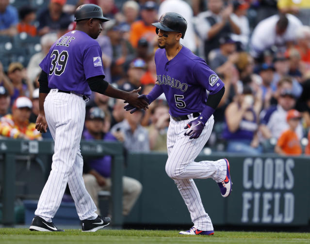Colorado Rockies third base coach Stu Cole, left, congratulates Carlos Gonzalez (5) as he circles the bases after hitting a solo home run off Houston Astros starting pitcher Charlie Morton during the second inning of a baseball game Wednesday, July 25, 2018, in Denver. (AP Photo/David Zalubowski)