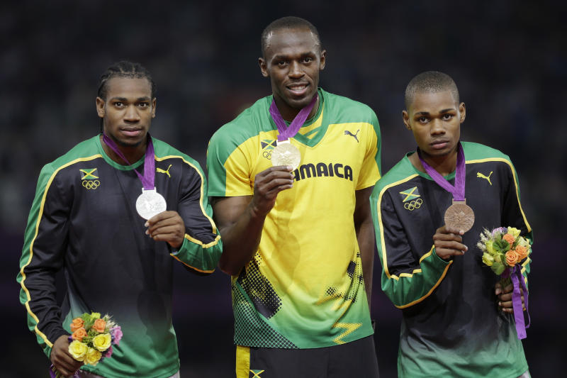 Jamaica's gold medal winner Usain Bolt is flanked by his teammates silver medal winner Yohan Blake, left, and bronze medalist Warren Weir during the ceremony for the men's 200-meter final during the athletics in the Olympic Stadium at the 2012 Summer Olympics, London, Thursday, Aug. 9, 2012.  (AP Photo/Matt Slocum)