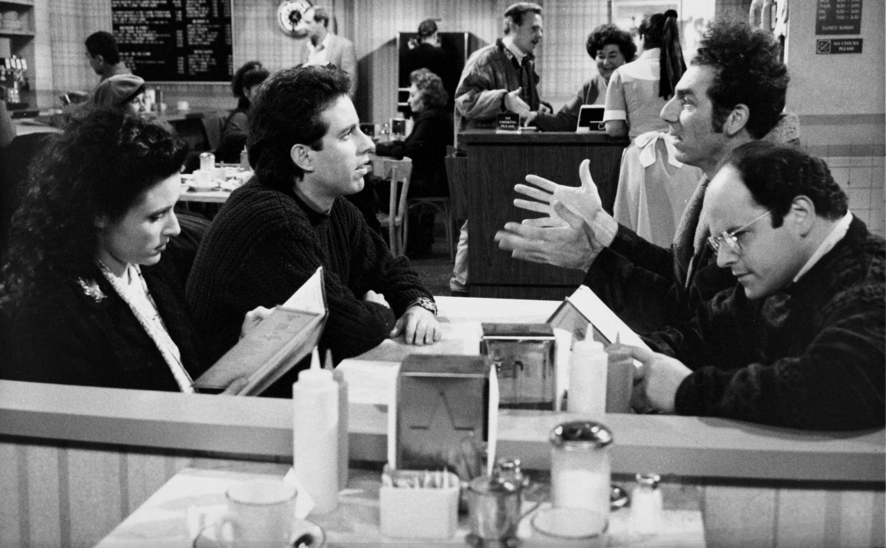"""SEINFELD -- """"The Kiss Hello"""" Episode 17 -- Pictured: (l-r) Julia Louis-Dreyfus as Elaine Benes, Jerry Seinfeld as himself, Michael Richards as Cosmo Kramer, Jason Alexander as George Costanza (Photo by Carin Baer/NBCU Photo Bank/NBCUniversal via Getty Images via Getty Images)"""