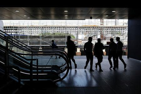 FILE PHOTO: People walk past the Crossrail construction site in the financial district of Canary Wharf in London