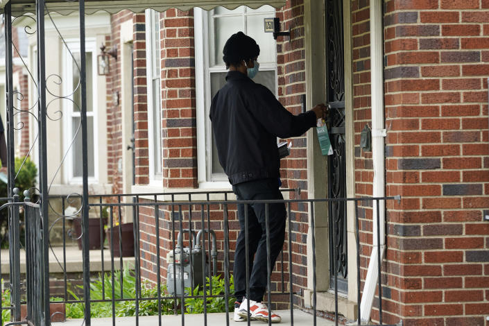 Deares Carey leaves a flyer on a home in Detroit, Tuesday, May 4, 2021. Officials are walking door-to-door to encourage residents of the majority Black city to get vaccinated against COVID-19 as the city's immunization rate lags well behind the rest of Michigan and the United States. (AP Photo/Paul Sancya)
