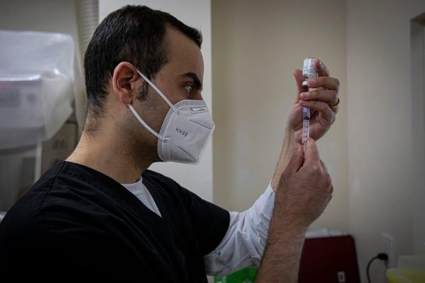 Pharmacist Kyro Maseh prepares a dose of the AstraZeneca COVID-19 vaccine at his pharmacy in Toronto on Tuesday. Toronto pharmacies began administering the vaccine to people born in 1981 and up on Tuesday.