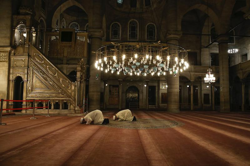 Imam of Eyup Sultan Mosque, Hasan Tok and Imam Metin Cakar hold a prayer for coronavirus in Istanbul, Friday, April 3, 2020. After the fifth and final call to prayer of the day in Muslim Turkey, imams around the country have been asked to perform an additional prayer asking for God's mercy and protection during the novel coronavirus pandemic. Calls echoed across the city of Istanbul, Turkey's largest, where thousands of people have been infected with the virus.