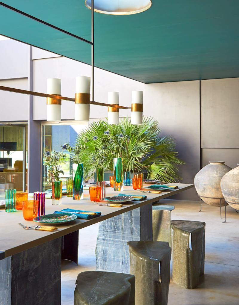In a covered outdoor area, fiberglass stools surround a marble table, all by De Cotiis. vintage ceramic plates; brass and white glass light by De Cotiis.