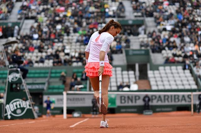 Poland's Agnieszka Radwanska removes clay from her shoes during her women's fourth round match against Bulgaria's Tsvetana Pironkova at the French Open in Paris on May 31, 2016 (AFP Photo/Philippe Lopez)